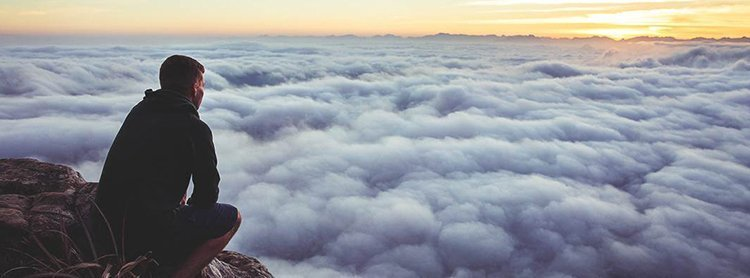 Man discerning looking above the clouds